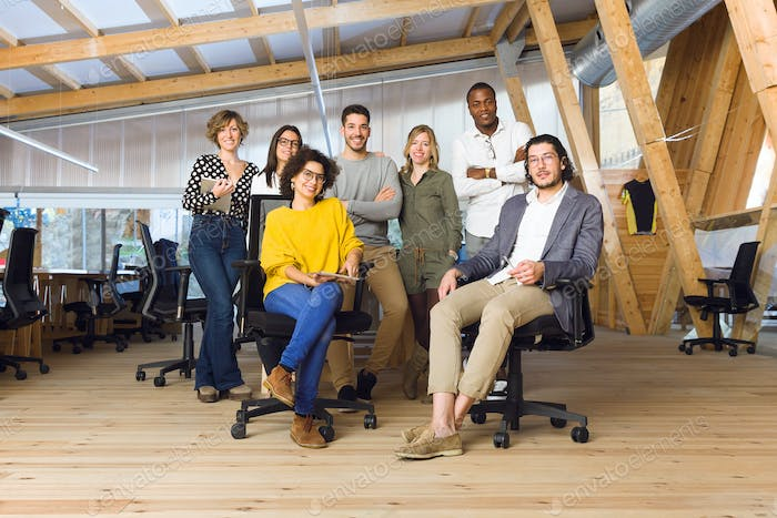 Young business team posing and looking at camera on coworking pl