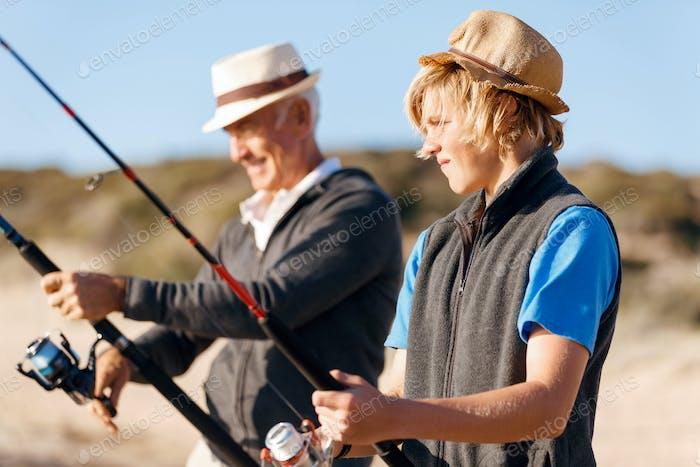 Senior Mann Angeln mit seinem Enkel