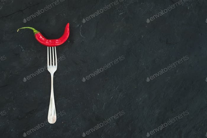 Red hot chili pepper on vintage silver fork over black slate stone background, top view.