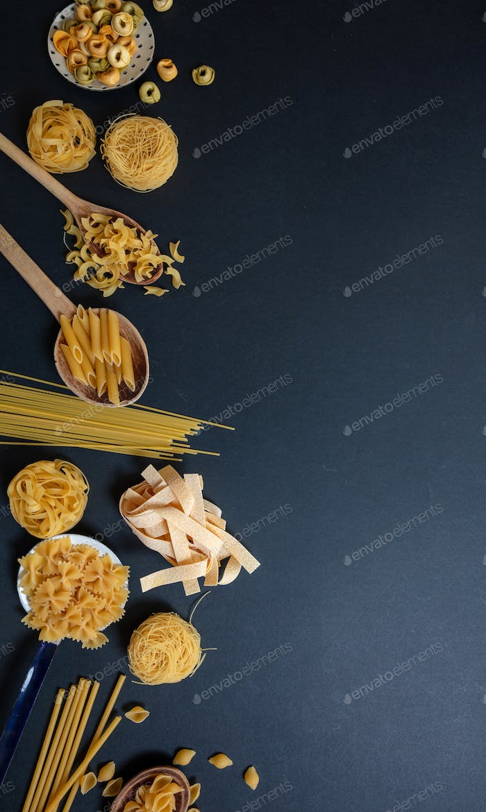 Pasta assortment on black background, top view. Cooking italian cuisine concept