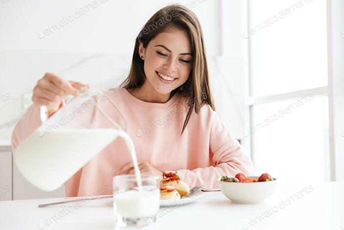 Schöne lächelnde junge Mädchen mit leckerem gesundem Frühstück