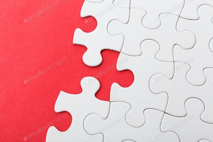 Weißes Puzzle auf rotem Hintergrund