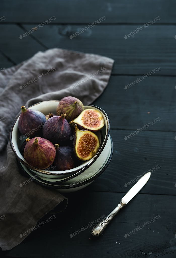 Rustic metal bowl of fresh figs on dark background, top view, selective focus.