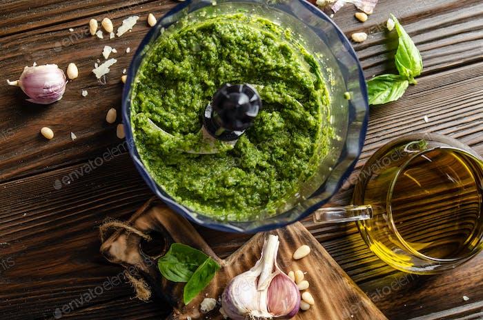 Flat lay view at italian national traditional genovese pesto sauce in food processor bowl