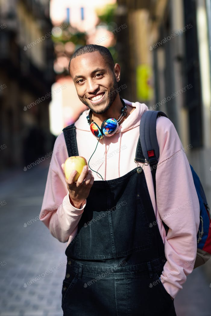 Young black man eating an apple walking down the street.