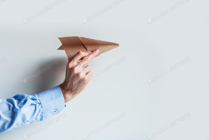 A male hand in a blue shirt uniform launches a paper airplane.