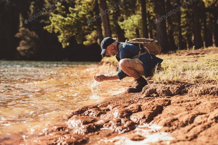 Reifer Mann waschen Gesicht aus See Wasser