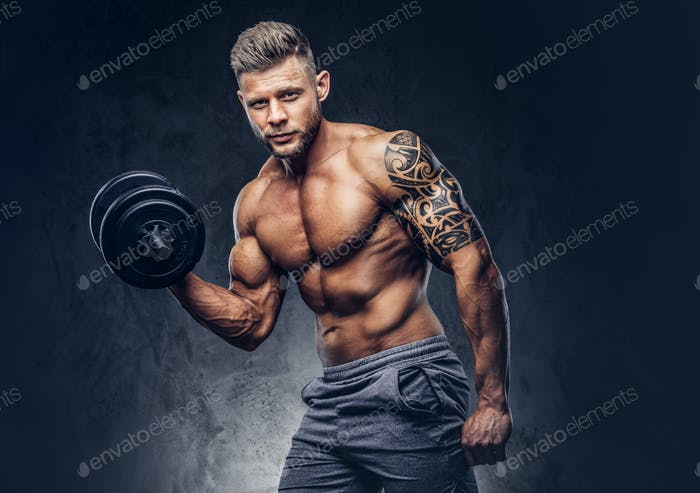 Handsome shirtless tattooed bodybuilder wearing sports shorts, posing in a studio.