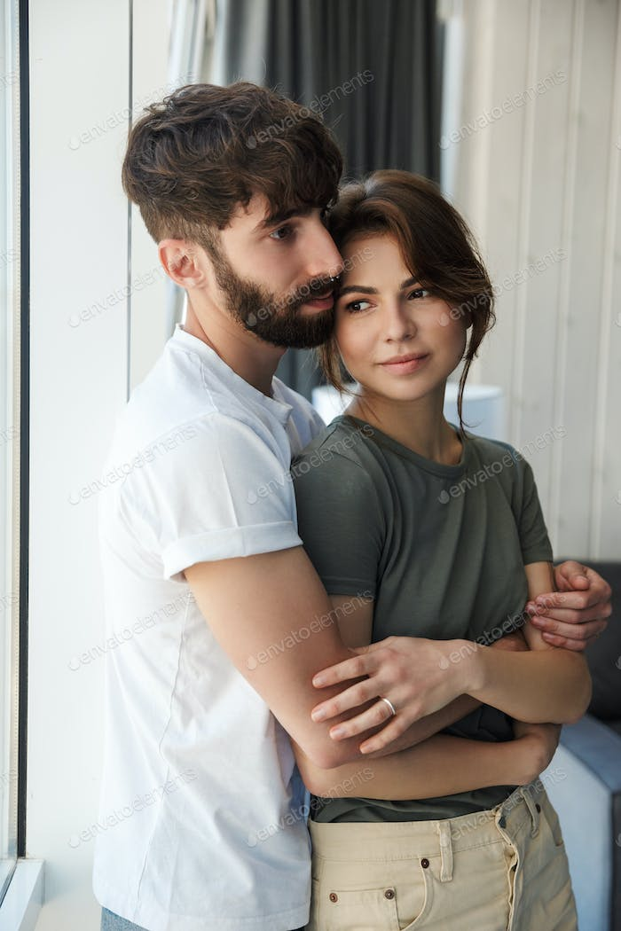 Lovely young couple embracing while standing at the window