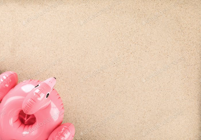 Inflatable Flamingo on a sand background.Trendy summer concept.Beach composition.