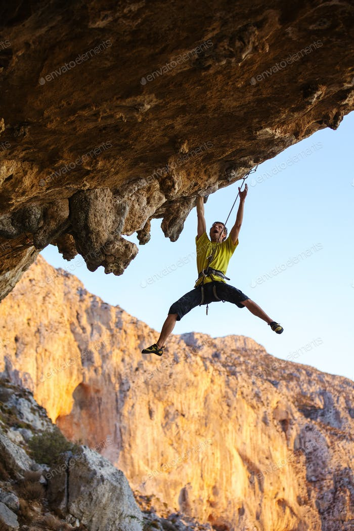 Rock climber struggling on challenging route on cliff