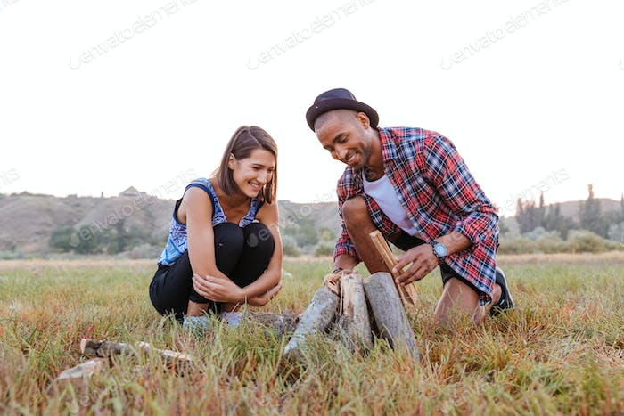 Multiethnic couple making campfire outdoors together