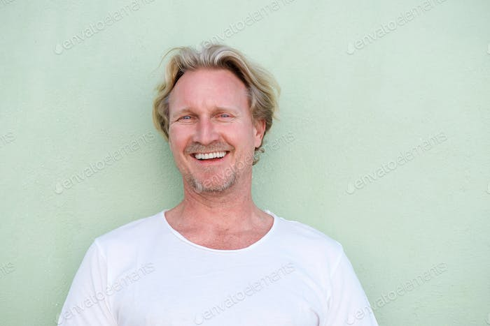 smiling middle aged man standing against green background