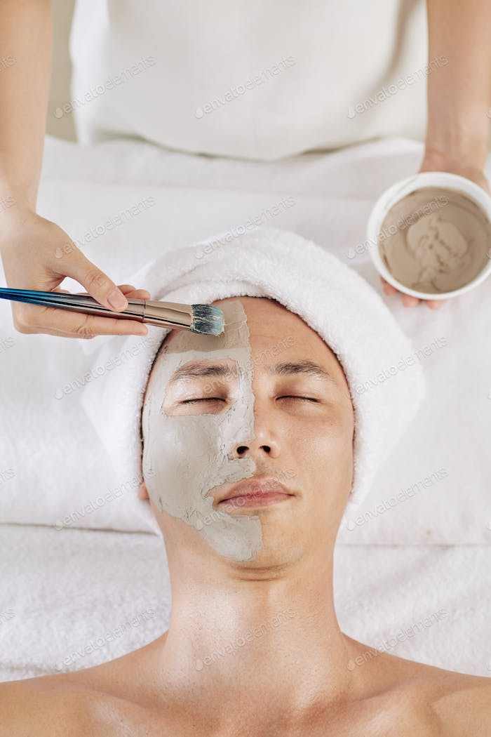 Beautician applying clay mask
