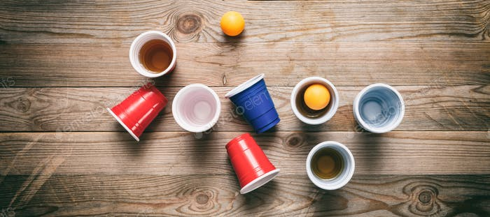 Beer pong. Plastic red and blue color cups and ping pong balls on wood, banner