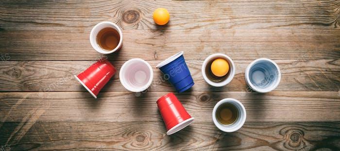 Bierpong. Kunststoff rot und blau Farbe Tassen und Tischtennisbälle auf Holz, Banner