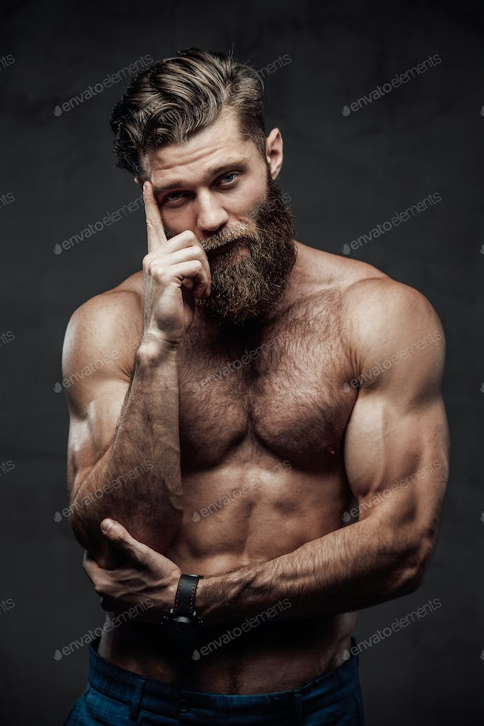 Brutal bearded guy posing with finger to his head