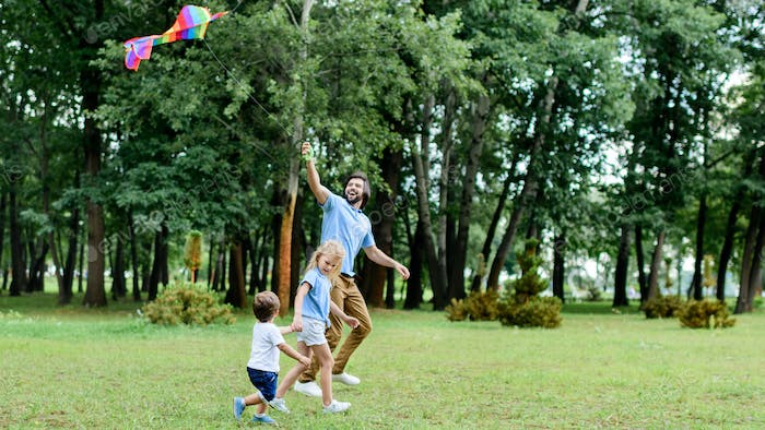 side view of handsome father and kids playing with kite at park