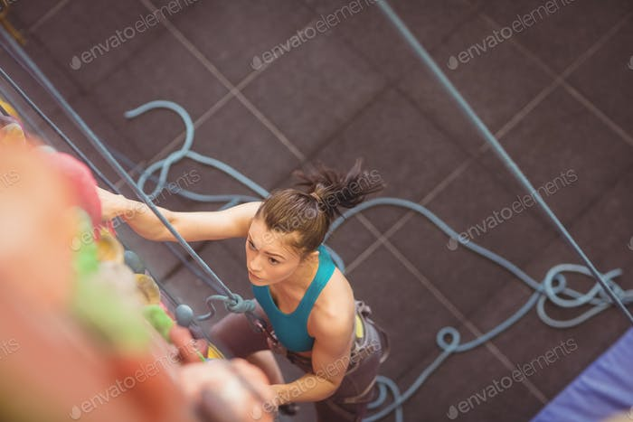 Woman climbing up rock wall at the gym