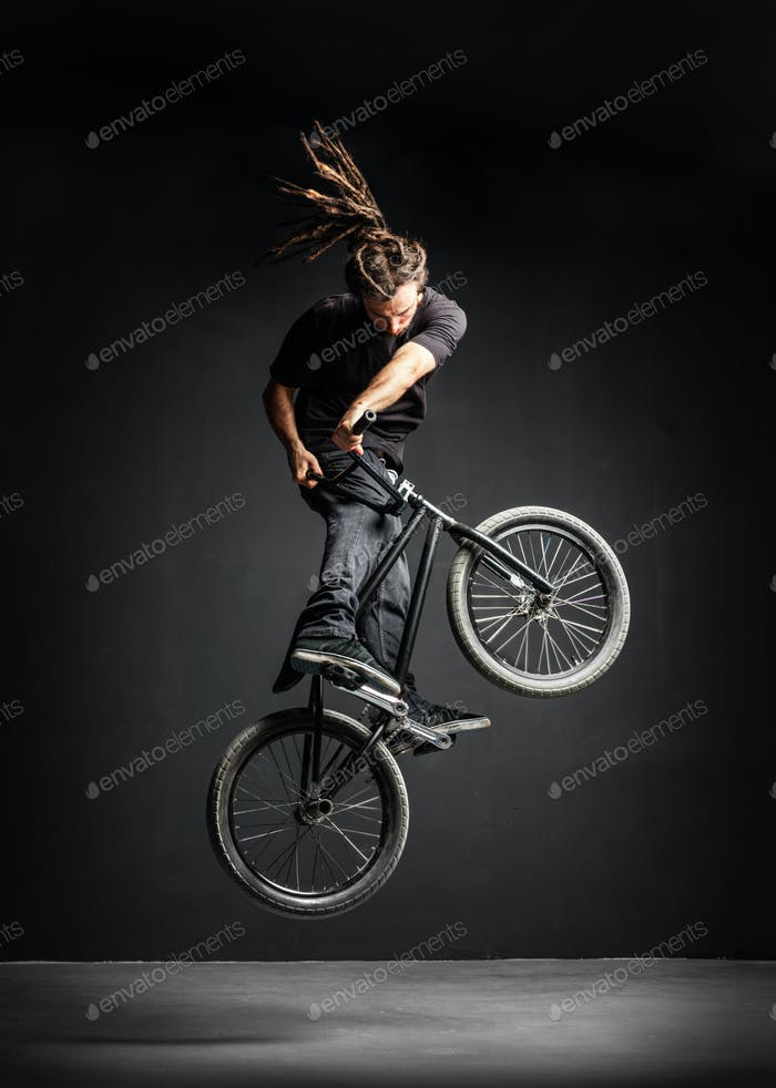 A man doing an extreme stunt on his BMX bicycle.