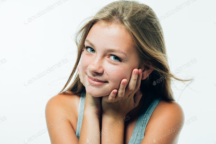 Beautiful teenager is touching her chin . Portrait of young girl with freckled face and long hair.