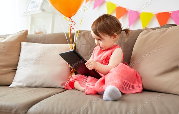 baby girl with tablet pc on birthday party at home