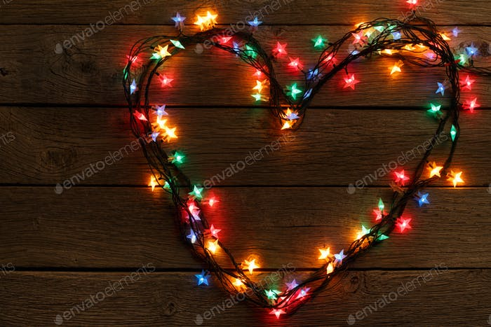 Heart from christmas lights on wood background