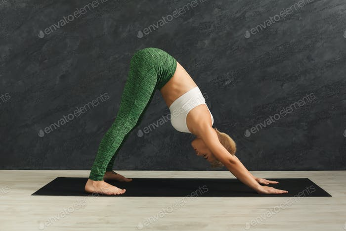 Woman training yoga in dog pose in gym