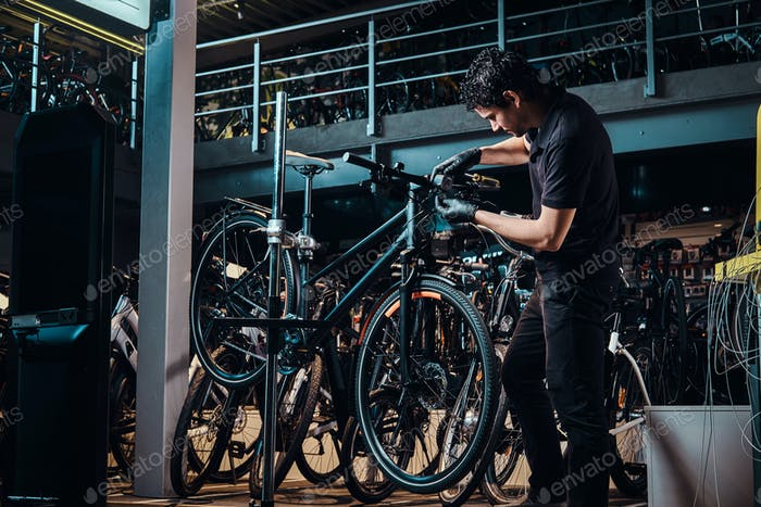 Expirienced young master is repairing customer's bicycle at workplace