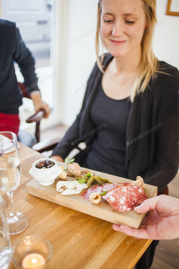 Cropped hand of waiter serving food to woman in restaurant