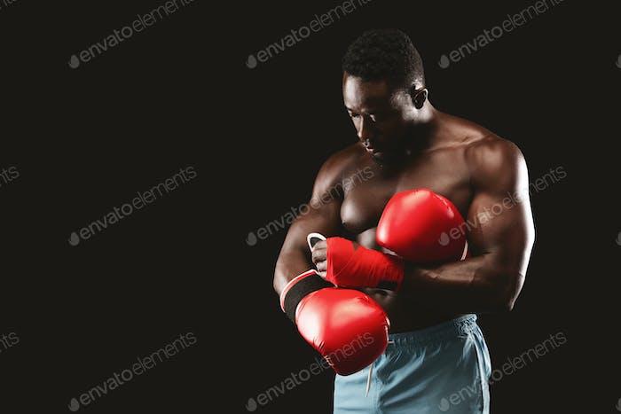 Schwarzer muskulöser Boxer trägt rote Handschuhe vor dem Kampf
