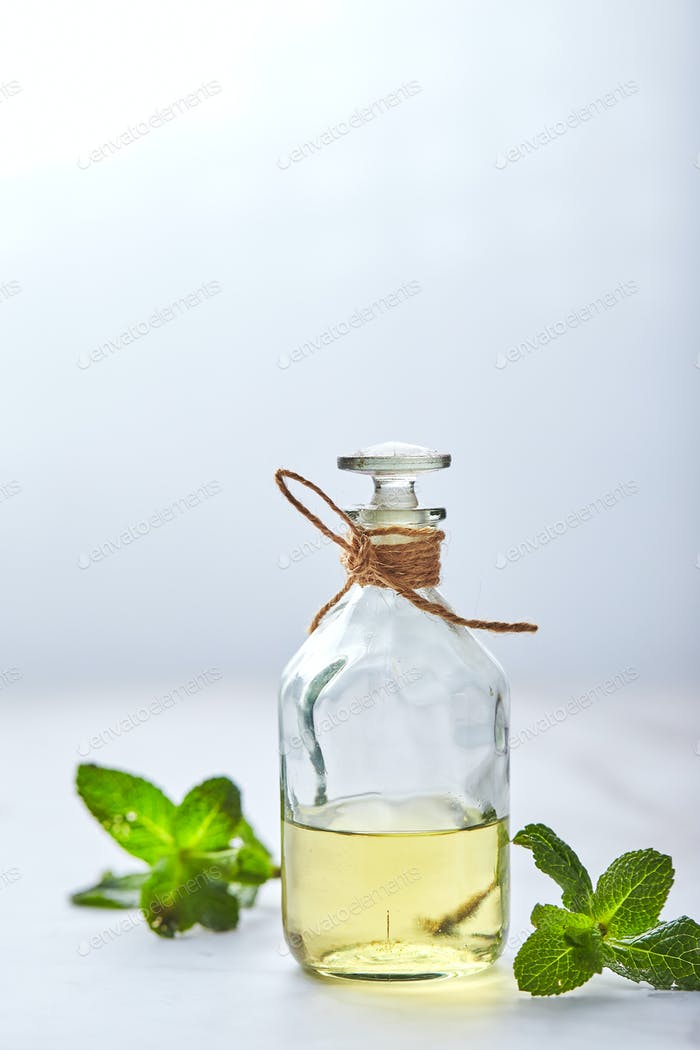 bottle with mint essential oil and green leaf on white background. Natual organic ingredients for