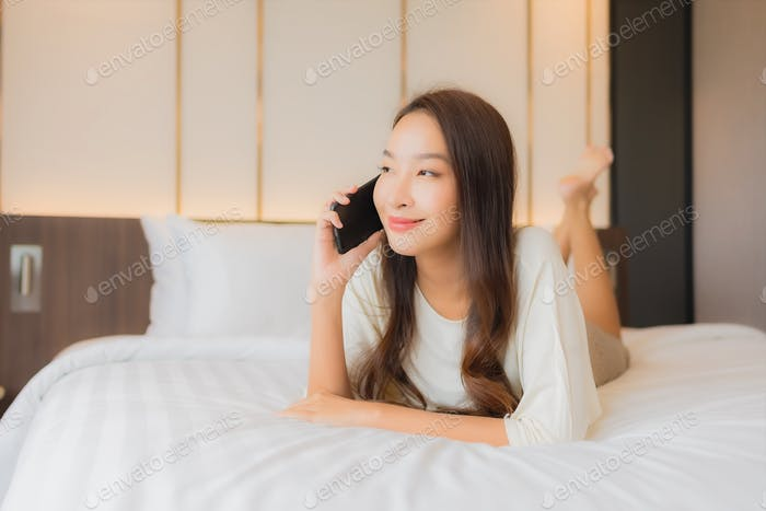 Portrait beautiful young asian woman use smart mobile phone on bed