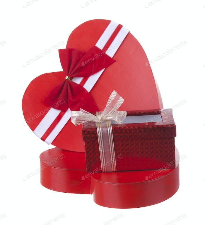 Rote Box in Herzform mit einer Geschenkbox isoliert auf weißem Hintergrund