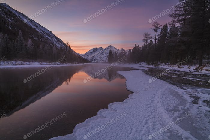 Beautiful winter landscape with mountains and a sunset sky.