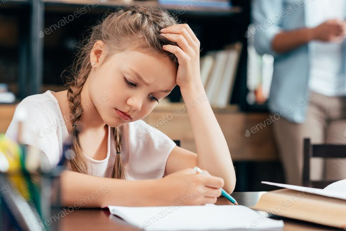 depressed little girl writing homework