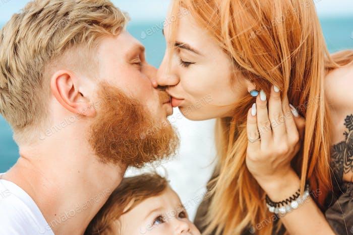 Mama und Papa küssen sich. Glückliche Familie im Urlaub