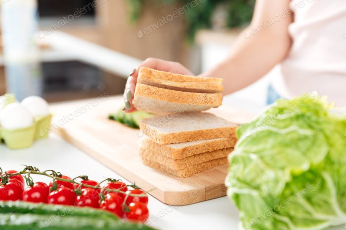 Frau, die Sandwiches mit Gemüse auf einem Schneidebrett macht