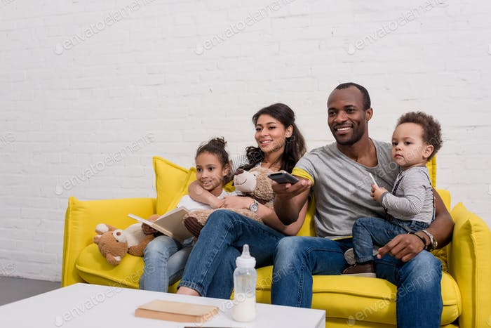 happy young family watching tv together on couch