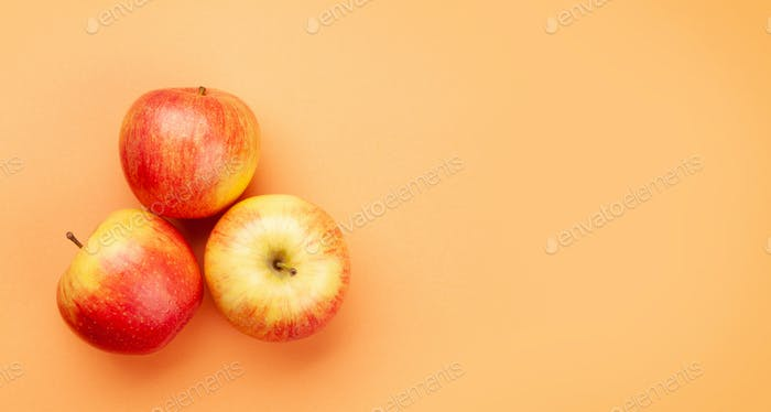 Fresh ripe red apple fruits on peach background