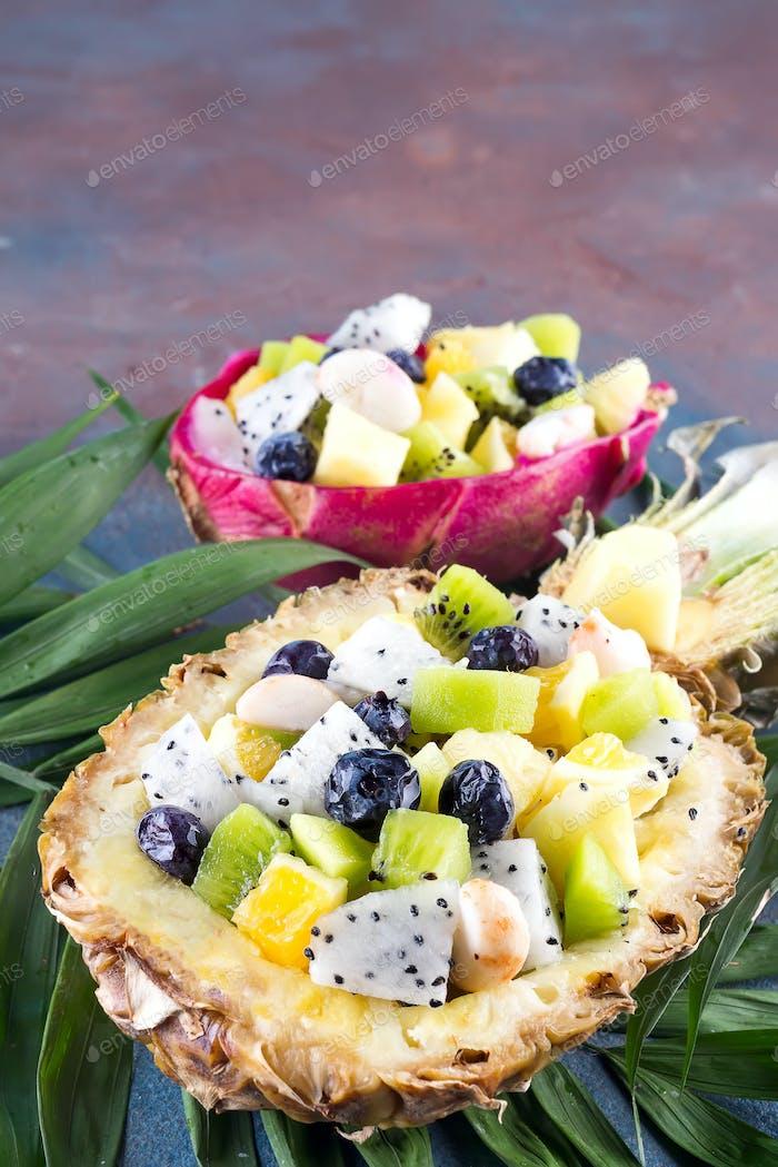 Exotischer Obstsalat in einer halben Ananas auf Palmblättern auf Steinhintergrund serviert. Gesunde Ernährung