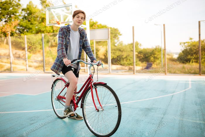 Young man in shorts and casual shirt standing with red bicycle on basketball court in park