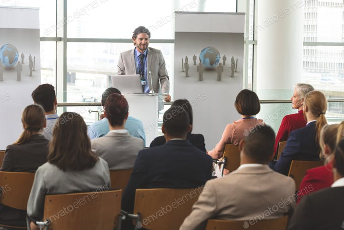 Businessman with laptop speaks at business seminar