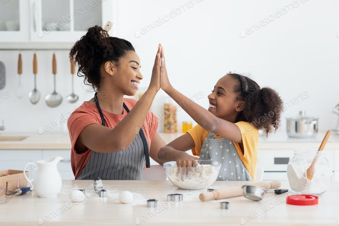 Cheerful black mother and daughter giving high five while cooking