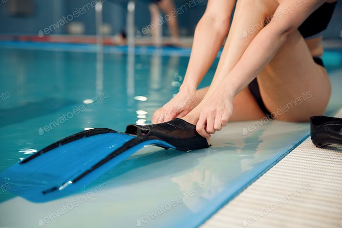 Female swimmer puts on flippers at the poolside