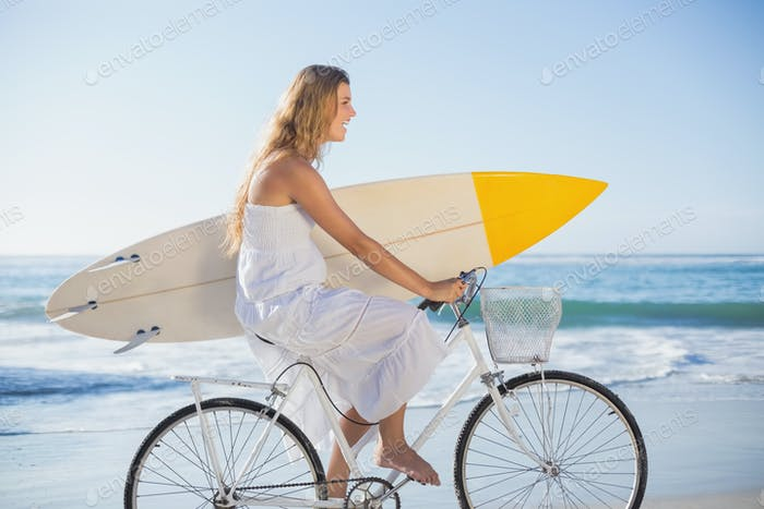 Beautiful surfer in sundress on bike holding surfboard at the beach on a sunny day