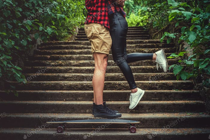 Casual moder young skateboarders couple posing on footway.