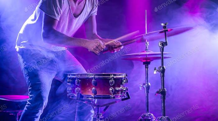 Ein Schlagzeuger spielt Schlagzeug auf blauem Hintergrund. Schöne Spezialeffekte von Licht und Rauch.