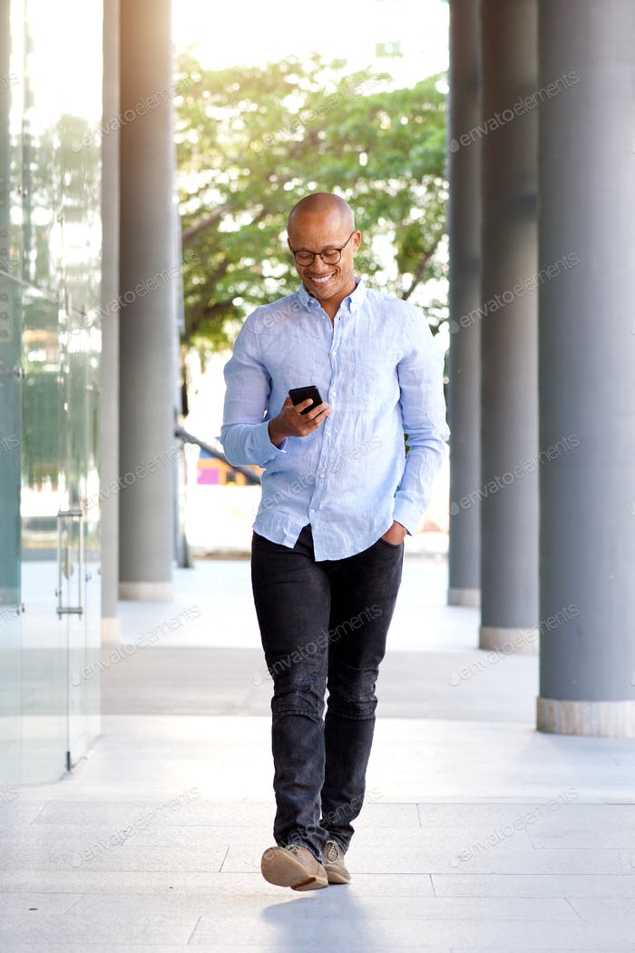 smiling african guy walking with mobile phone