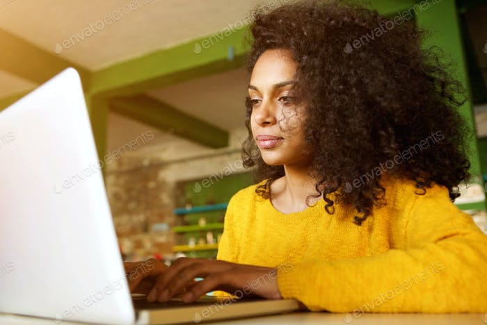 African lady working on laptop in a cafe